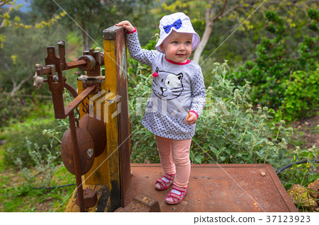 Little girl walking in the orange garden of Crete 37123923