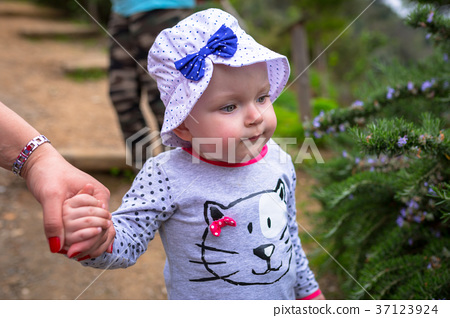 Little girl walking in the orange garden of Crete 37123924