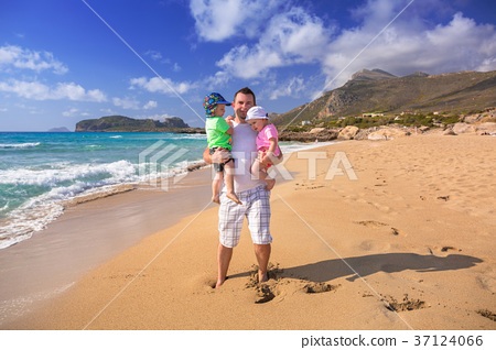 Father with twins on the beach holidays in Greece 37124066