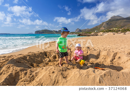 Twins playing in the sand on holidays in Greece 37124068