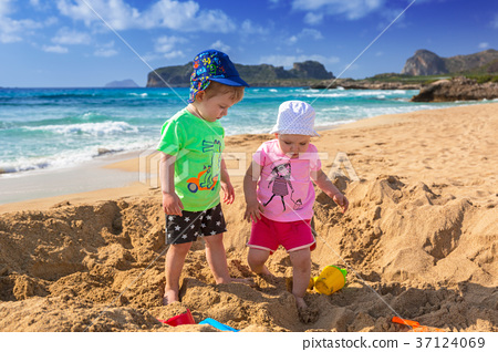 Twins playing in the sand on holidays in Greece 37124069