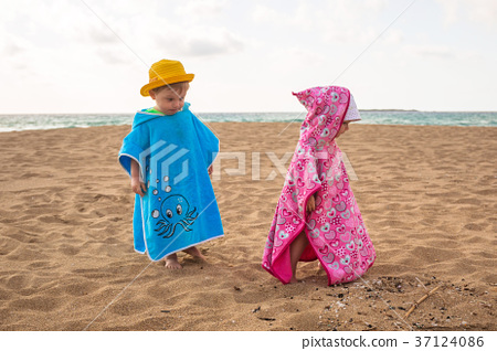 Little boy and girl twins walking on the beach 37124086