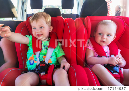 Little boy and girl twins seating in the car  37124087