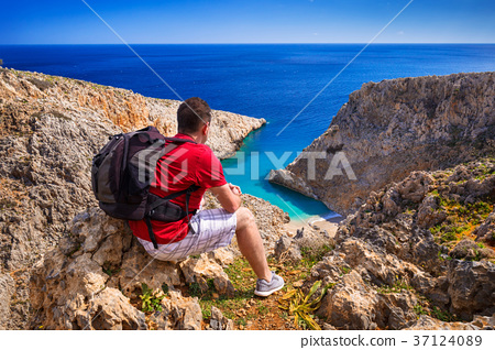Man with backpack watching beautiful beach  37124089