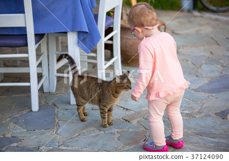 Little girl with a cat outdoor 37124090