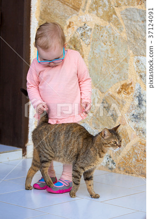 Little girl with a cat outdoor 37124091