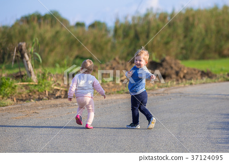 Little boy and girl twins running on the road  37124095