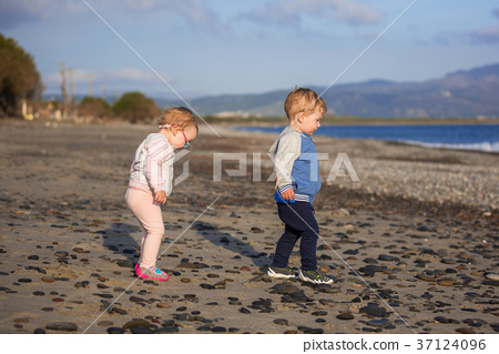 Little boy and girl twins walking on the beach  37124096
