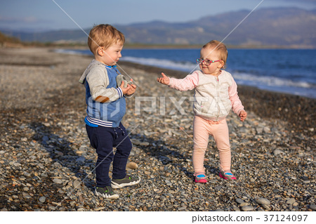 Little boy and girl twins walking on the beach  37124097