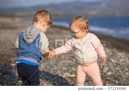 Little boy and girl twins walking on the beach  37124098