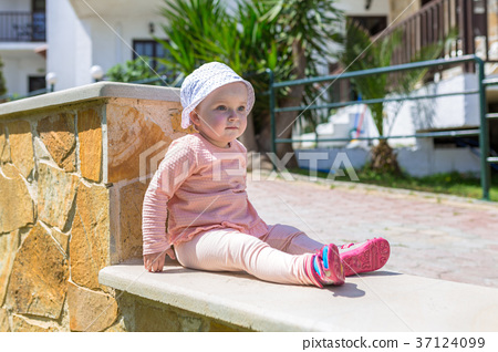 Girl sitting on the sunny wall on Crete, Greece 37124099
