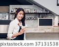 Asian female barista holding take away cup 37131538