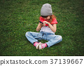 little girl with mobile phone on the grass 37139667