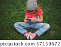 little girl with mobile phone on the grass 37139672