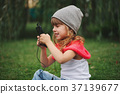 little girl with mobile phone on the grass 37139677
