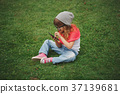 little girl with mobile phone on the grass 37139681