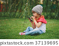 little girl with mobile phone on the grass 37139695