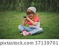 little girl with mobile phone on the grass 37139701