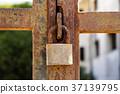 Closeup a blue rusty old metal door locked with a 37139795