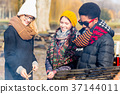 Group of young people roasting sausages outdoors 37144011