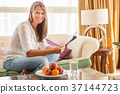 Woman on the couch with a magazine 37144723