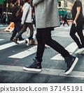 Man walking on crosswalk in the city street crowd 37145191
