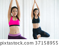 Women exercising yoga pose in fitness gym class 37158955