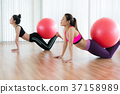 Women doing exercise with fit ball in gym class 37158989