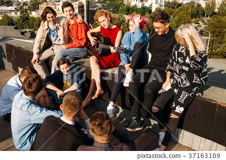 youth travel europe sit rooftop sing enjoy smile 37163109