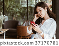 woman holding smartphone and listening to music with headphones at cafe. leisure, lifestyle, people concept 37170781