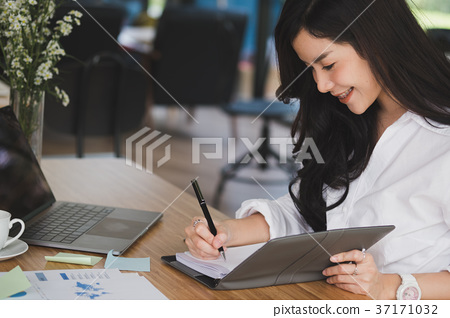 businesswoman write note on notebook at workplace. startup woman working with business plan report document at office. young female entrepreneur analyze accounting market data. financial adviser with paperwork on table. 37171032