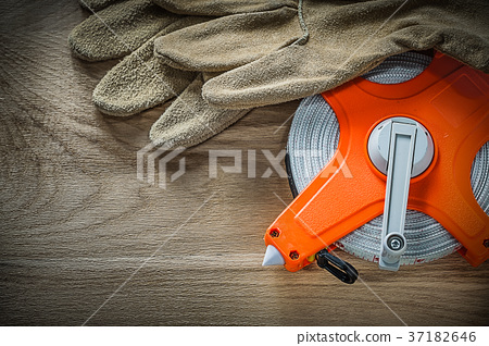 Leather safety gloves tape measure on wooden board 37182646