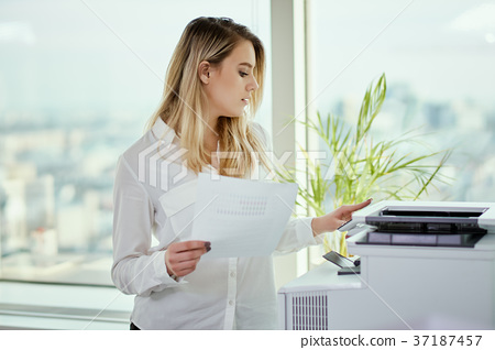 young businesswoman prints on the printer in the office 37187457