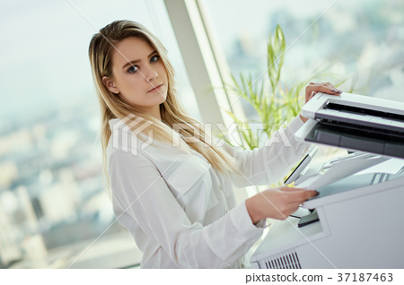 young businesswoman uses a scanner in a skyscraper office 37187463