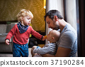 Father with a toddler boy and a baby in a hotel 37190284
