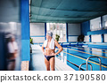 Senior man standing by the indoor swimming pool. 37190580