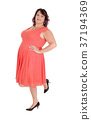 A plus size woman standing in a red dress 37194369