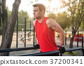 Fit man workout out arms on dips horizontal bars 37200341
