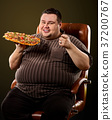 Fat man eating fast food pizza. Breakfast for 37200767
