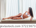 Smiling slim young brunette woman wearing white 37223673