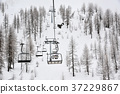 a chairlift climbs over the snow-capped mountains 37229867