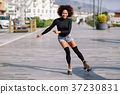 Black woman on roller skates riding outdoors on urban street 37230831