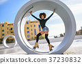 Black woman on roller skates riding outdoors on urban street 37230832