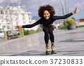 Black woman on roller skates riding outdoors on urban street 37230833