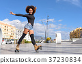 Black woman on roller skates riding outdoors on urban street 37230834
