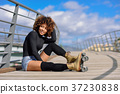 Afro hairstyle woman on roller skates sitting on urban bridge 37230838