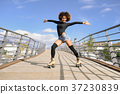 Afro hairstyle woman on roller skates riding outdoors on urban b 37230839