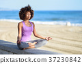 Black woman, afro hairstyle, in lotus pose with eyes closed in t 37230842