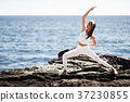 Young woman doing yoga in the beach wearing white clothes 37230855