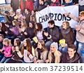 Cheering fans in stadium holding champion banner. 37239514
